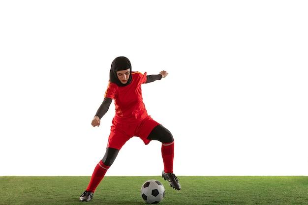 Arabian female football player isolated on white studio wall