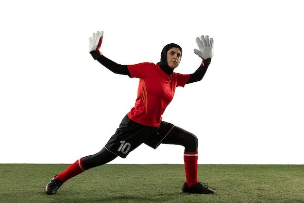 Calcio femminile arabo o giocatore di football americano, portiere su sfondo bianco studio. giovane donna che cattura palla, formazione, protezione degli obiettivi in movimento e in azione. concetto di sport, hobby, stile di vita sano.
