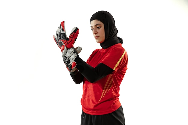 Arabian female soccer or football player, goalkeeper on white studio background. young woman preparing for game, training,, protecting goals for team. concept of sport, hobby, healthy lifestyle.