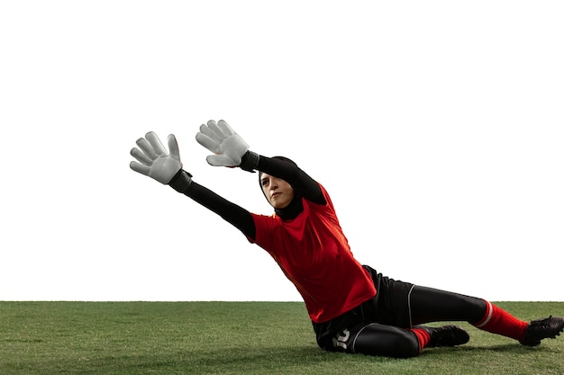 Arabian female soccer or football player, goalkeeper on white studio background.