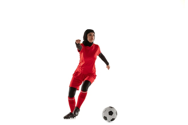 Arabian female soccer or football player isolated on white studio background. young woman kicking the ball, training, practicing in motion and action.