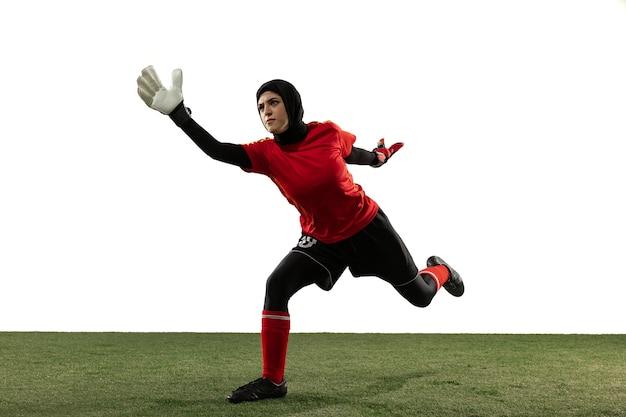 アラビアの女性のサッカーまたはサッカー選手、白いスタジオの背景にゴールキーパー。ボールをキャッチし、トレーニングし、動きと行動の目標を保護する若い女性。スポーツ、趣味、健康的なライフスタイルの概念。