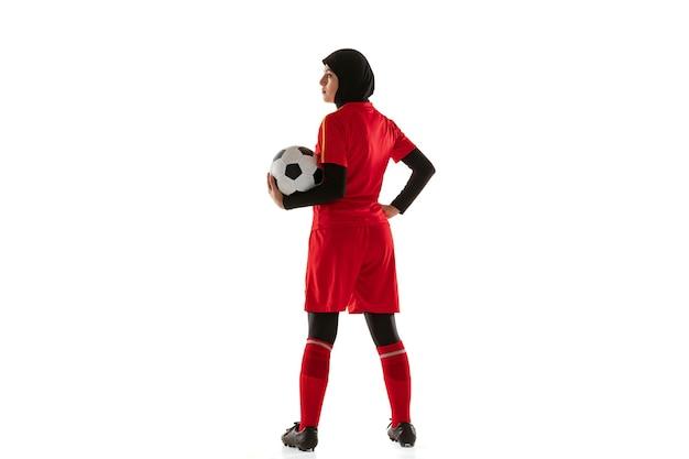 白いスタジオの背景に分離されたアラビアの女性サッカーまたはサッカー選手。ボールを持って、トレーニングし、動きと行動で練習している若い女性。