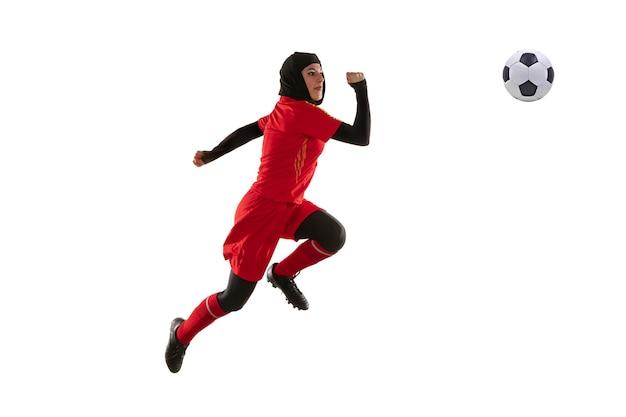 白いスタジオの背景に分離されたアラビアの女性サッカーまたはサッカー選手。ジャンプでボールを蹴る若い女性、空中でキャッチ、動きのトレーニング、アクション。