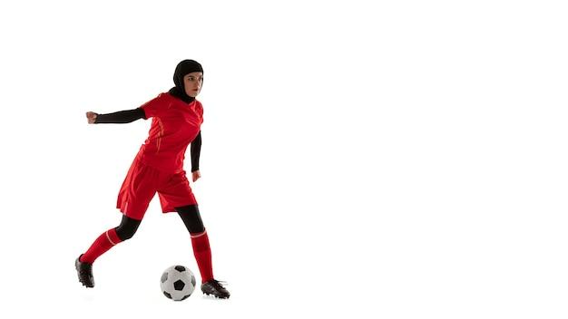白いスタジオの背景に分離されたアラビアの女性サッカーまたはサッカー選手。ボールを蹴る若い女性、動きのトレーニング、アクション。チラシ、フライシート。
