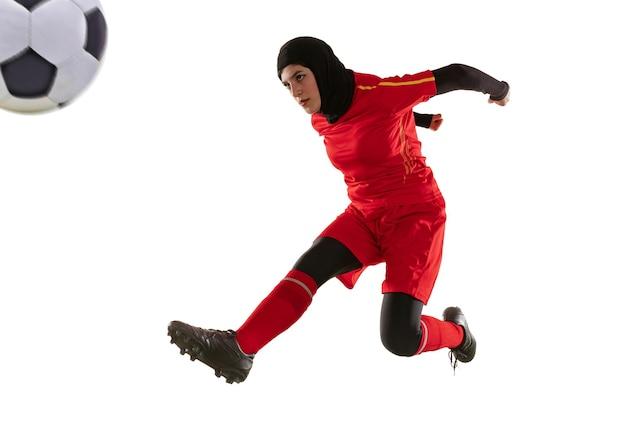 아라비아 여성 축구 또는 축구 선수 흰색 스튜디오 배경에 고립. 공을 차고, 훈련, 모션 및 행동 연습 젊은 여자.