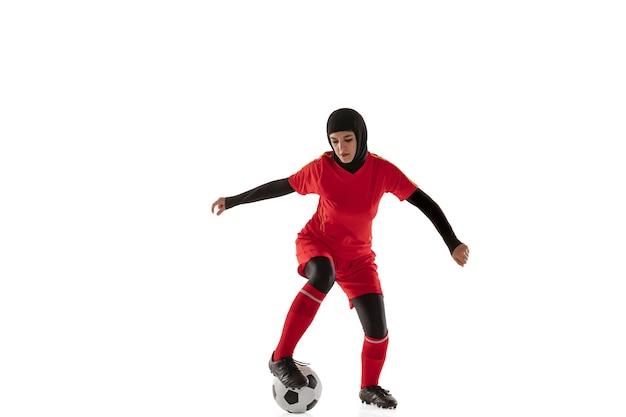 白いスタジオの背景に分離されたアラビアの女性サッカーまたはサッカー選手。ボールを蹴り、トレーニングし、動きと行動の練習をしている若い女性。