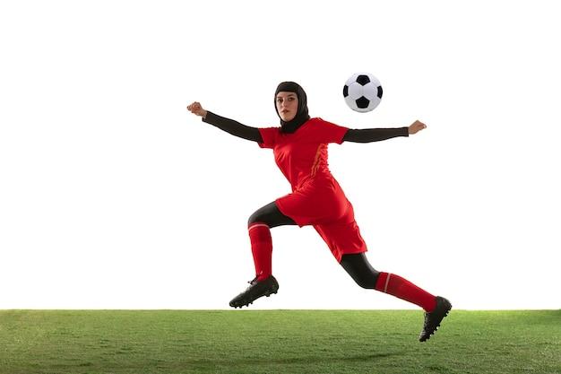 Arabian female soccer player isolated on white studio wall