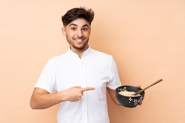 ベージュで隔離され、箸で麺のボウルを保持しながらそれを指しているアラビアのハンサムな男