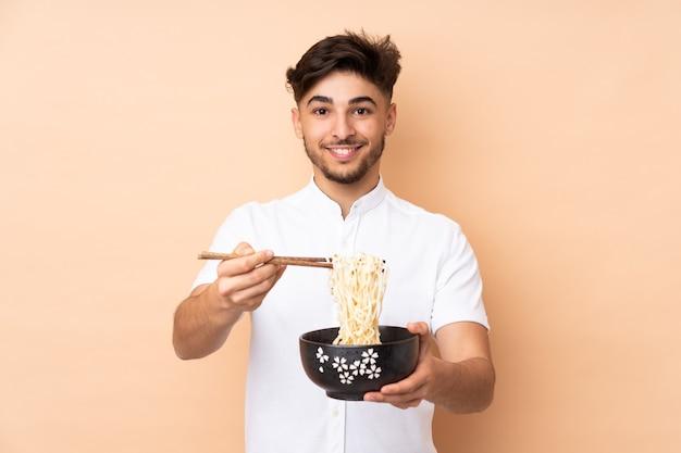 箸で麺のボウルを保持しているベージュで隔離のアラビアのハンサムな男