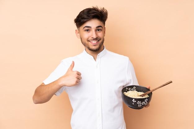 箸で麺のボウルを保持しているときに何か良いことが起こったので、親指を立ててベージュで孤立したアラビアのハンサムな男