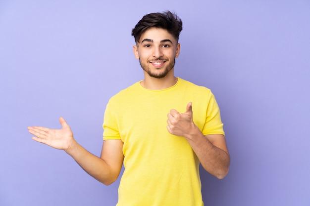 広告を挿入し、親指を立てて手のひらに架空のコピースペースを保持している孤立した上のアラビアのハンサムな男