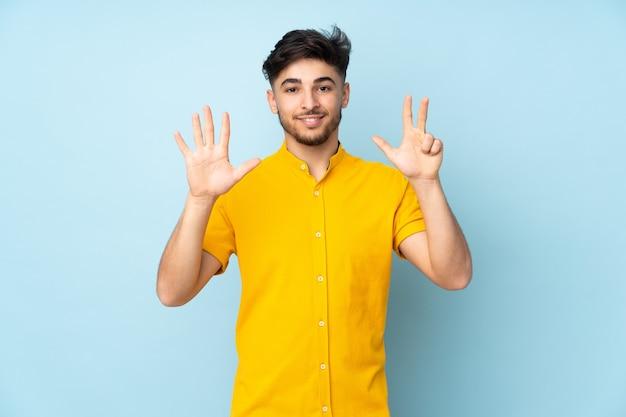 指で8を数える孤立した壁の上のアラビアのハンサムな男