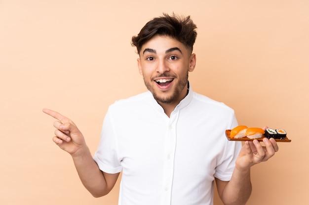 Арабский мужчина ест суши, изолированный на бежевом, удивлен и показывает пальцем в сторону