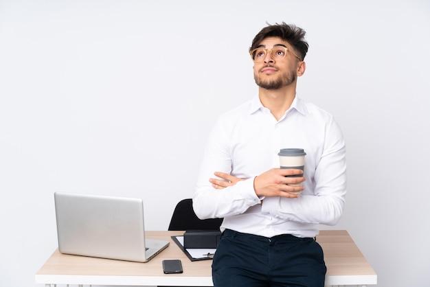 Арабский мужчина в офисе, изолированном на белом, глядя вверх, улыбаясь