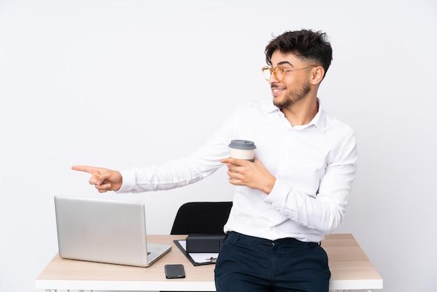横に指を指し、製品を提示する白い壁に隔離されたオフィスでアラビア人男性