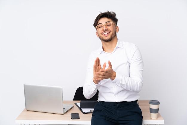 Арабский мужчина в офисе на белой стене аплодирует после презентации на конференции