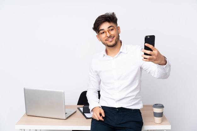 Selfieを作る白い壁のオフィスでアラビア人