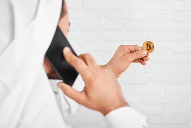 An arabian man keeps golden bitcoin in one hand and talks on the mobile phone with another