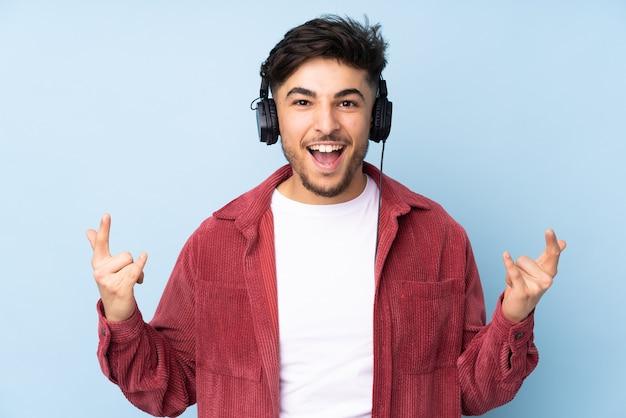 Арабский мужчина слушает музыку, делая рок-жест