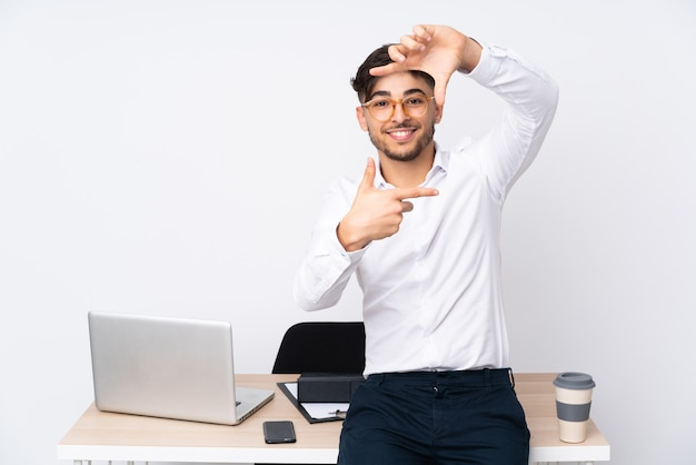 Arabian man in a office on white wall making a frame with fingers