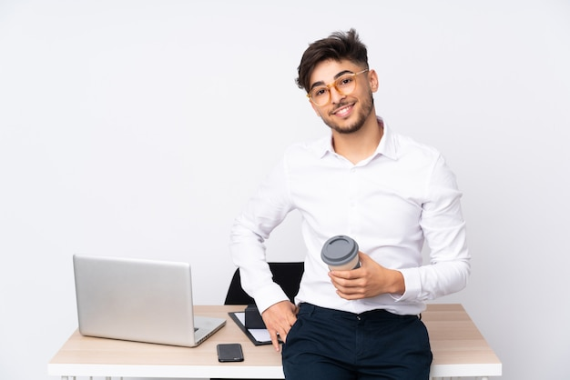 Arabian man in a office on white wall posing with arms at hip and smiling