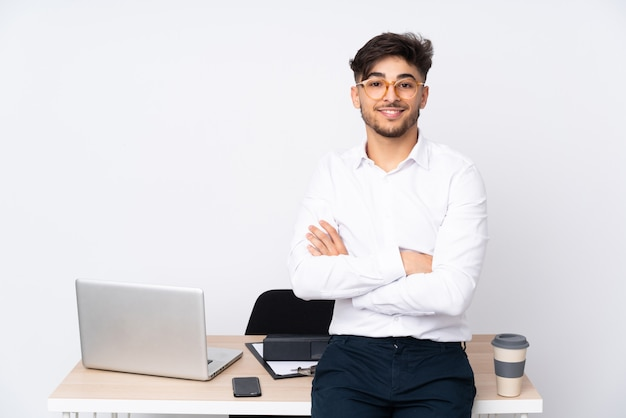 Arabian man in a office on white wall with arms crossed and looking forward