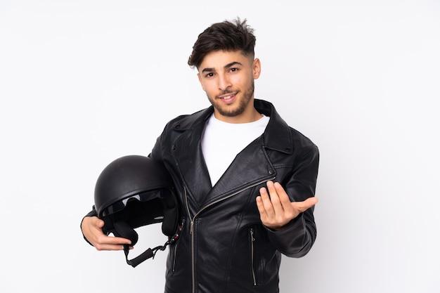 手で来るように誘う白い壁に隔離されたオートバイのヘルメットを持つアラビア人。あなたが来て幸せ