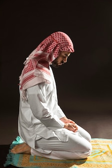 Arabian man with kandora sitting on prayer rug sideways