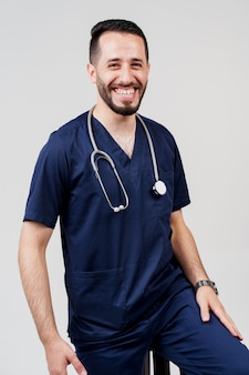 Arabian medical student with stethoscope in surgical uniform smiles