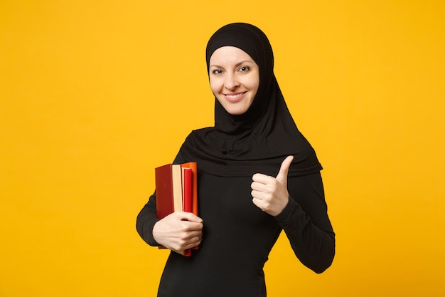 Arabian muslim student girl in hijab black clothes holds books isolated on yellow wall  portrait. people religious lifestyle, education in high school concept. .