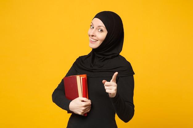 ヒジャーブの黒い服を着たアラビアのイスラム教徒の学生の女の子は、黄色の壁の肖像画に分離された本を保持しています。人々の宗教的なライフスタイル、高校の概念の教育。 。