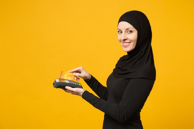 Arabian muslim woman in hijab black clothes hold payment terminal to process and acquire credit card payments isolated on yellow wall . people religious lifestyle concept.