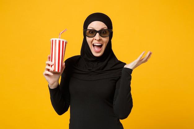 Арабская мусульманка в черной одежде хиджаба 3d очки imax смотреть фильм фильм держать бумажный стаканчик содовой изолирован на портрете желтой стены. концепция образа жизни людей. .