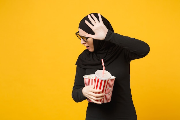 Арабская мусульманка в черной одежде хиджаба 3d очки imax смотреть фильм фильм держать попкорн, чашка содовой изолирована на портрете желтой стены. концепция образа жизни людей. .
