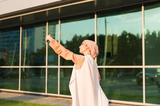 屋外でスマートフォンで自分撮りをしているアラビアのイスラム教徒の女性
