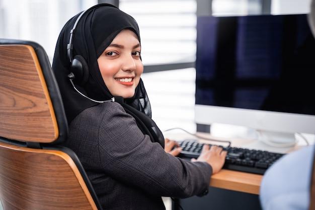 アラビア人またはイスラム教徒の女性がコンピューターで作業しているマイクヘッドセットを身に着けているコールセンターのオペレーターとカスタマーサービスエージェントで働いており、サービス精神を支援するために顧客と話している