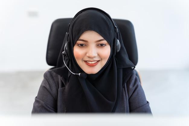 アラビア人またはイスラム教徒の女性は、コールセンターのオペレーターとカスタマーサービスエージェントで、コンピューターで動作するマイクヘッドセットを装着して働いており、サービスマインドを支援するために顧客と話し合っています。