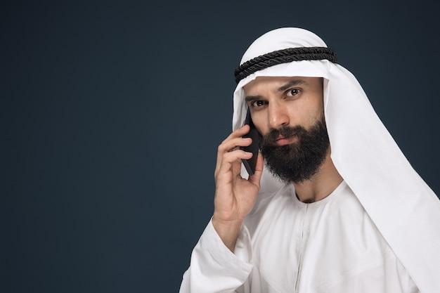 Uomo arabo saudita su sfondo blu scuro per studio