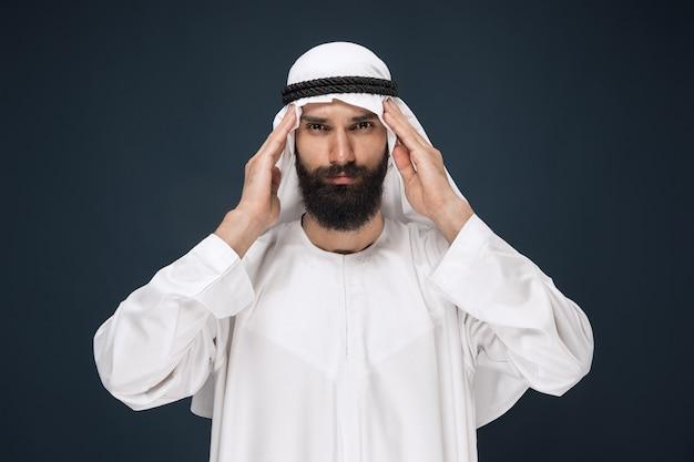 Uomo arabo saudita su studio blu scuro