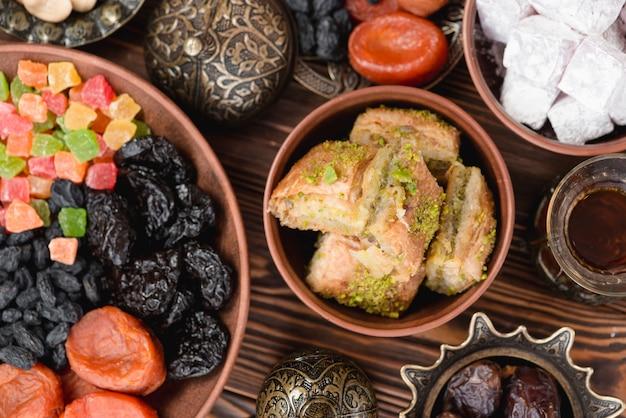 Арабские сладости для рамадан пахлавы; лукум и сухофрукты на тарелке над столом