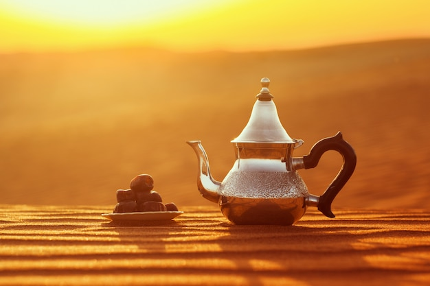 Arabian teapot and dates in the desert at a beautiful sunset symbolizing ramadan