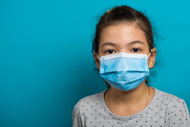 青い背景の上の医療マスクのアラビアの幼児の女の子。閉じる。