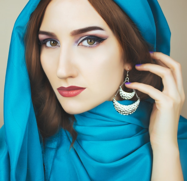 Arabian woman in the blue scarf closeup on the brown wall