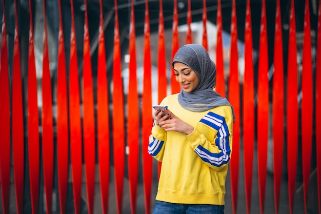 Arabian woman in hijab ouside in the street using phone