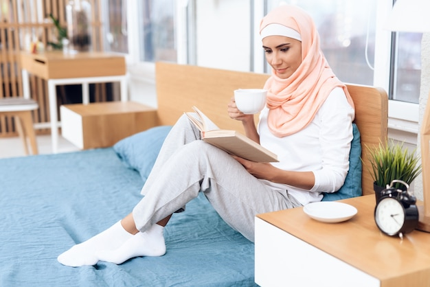 Arabian woman is drinking tea and reading a book