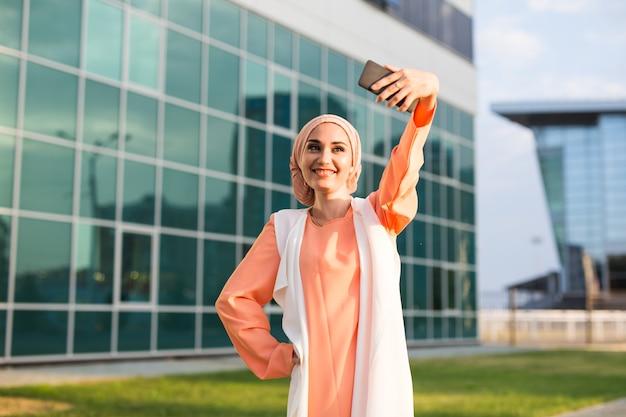 Arabian woman taking selfie. young beautiful muslim woman walk in the city.
