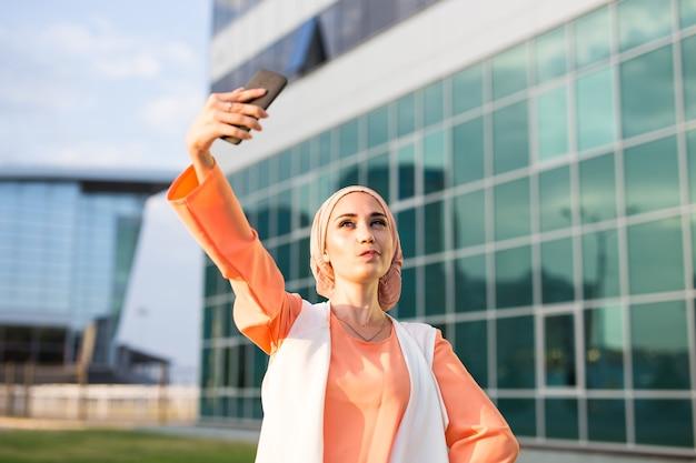 自撮りをしているアラビアの女性。若い美しいイスラム教徒の女性が街を歩きます。