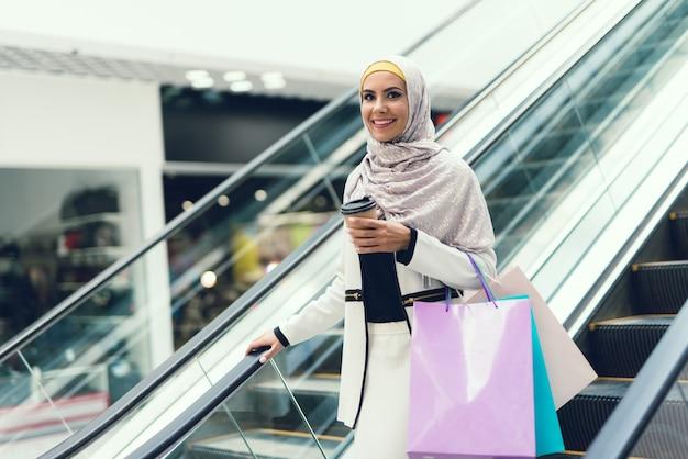 Арабская женщина женщина в хиджабе с чашкой кофе в торговом центре.