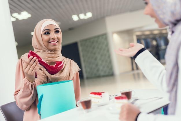 Arabian women sitting in cafe in modern mall.
